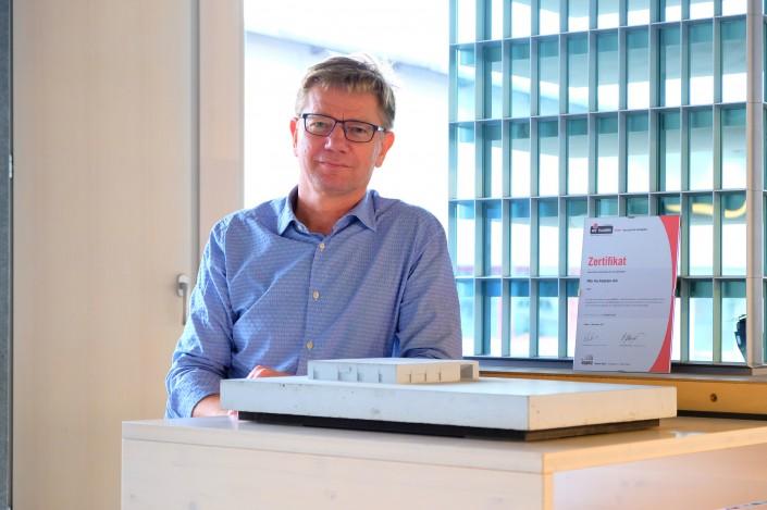 Das Foto zeigt ffbk Architekten AG Geschäftsführer Jan Krarup mit dem Label iPunkt Zertifikat