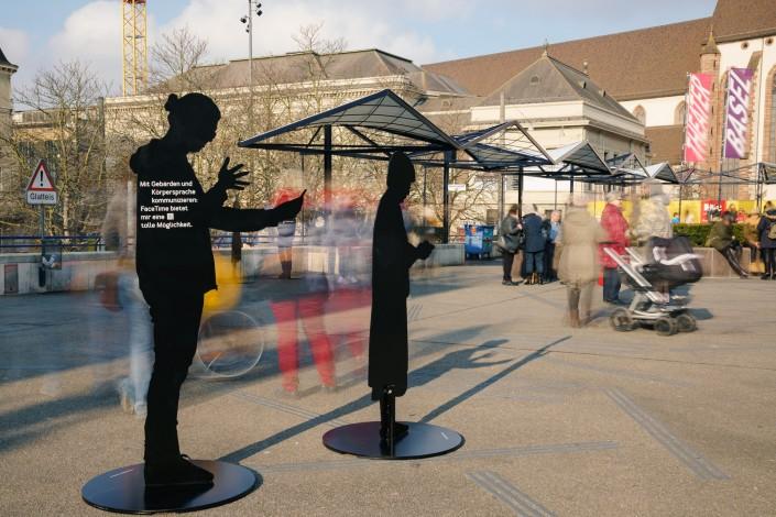 Das Foto zeigt 2 Silhouetten auf dem Basler Theaterplatz